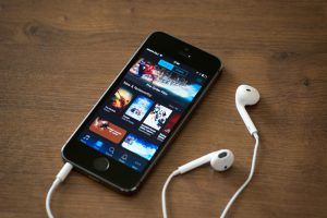 Kiev, Ukraine - June 5, 2014: Brand new Apple iPhone 5S with iTunes store application on the screen lying on a desk with headphones. iTunes is the media library with player for download and organize media files, developed by Apple Inc.