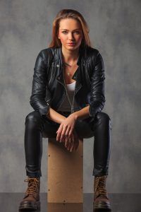 rocker in black leather jacket posing seated in studio background looking at the camera and resting